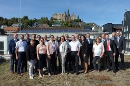 Die 26 Aussteller bei ihrem Vortreffen in den Räumen der Sparkasse-Marburg-Biedenkopf vor der Kulisse des Landgrafenschlosses