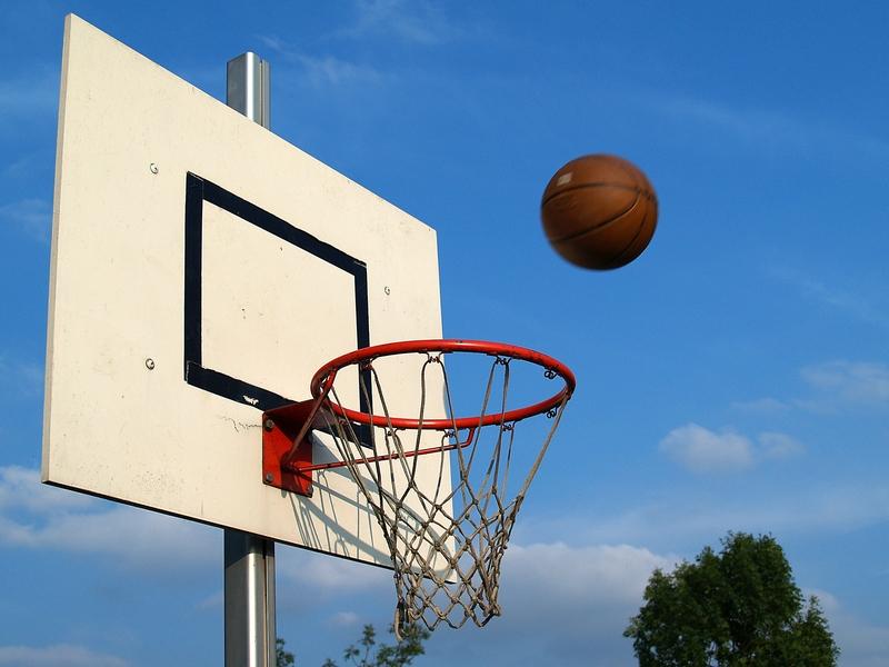 Basketball fliegt auf einen Basketballkorb zu