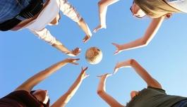 Gruppe junger Menschen wirft einen Ball in die Höhe