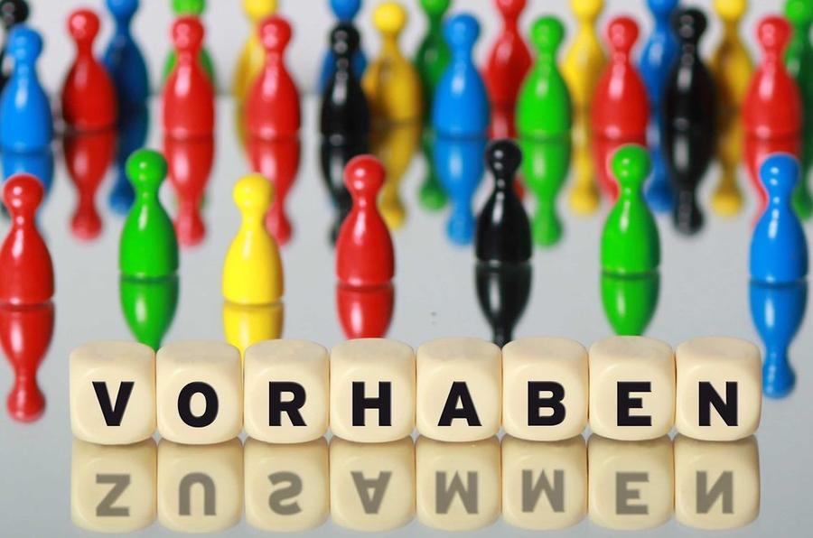 Vorhaben in der Stadt Gießen - Spielfiguren sind hinter acht Würfeln mit den Buchstaben VORHABEN angeordnet