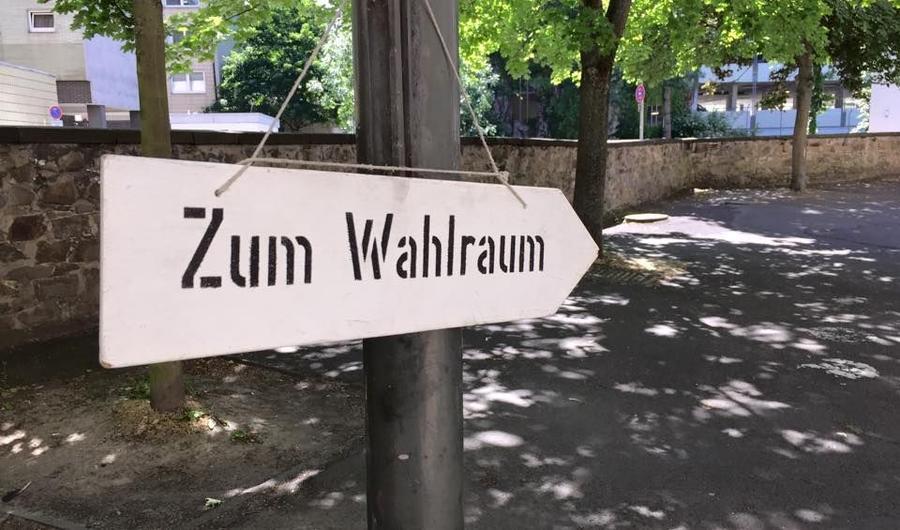 """Hinweisschild mit der Aufschrift """"Zum Wahlraum"""""""