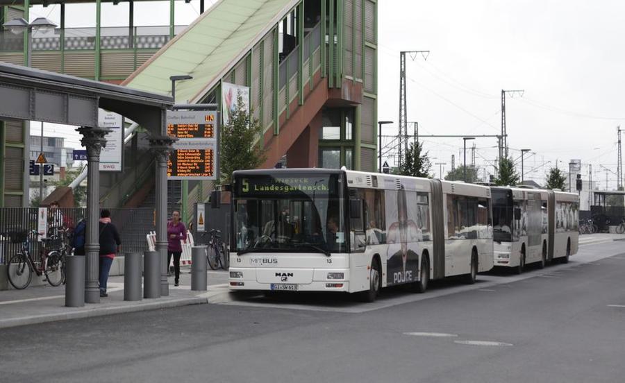 Busse der MitBus warten am Bahnhof - im Vordergrund die digitale Anzeigentafel mit den Abfahrtszeiten