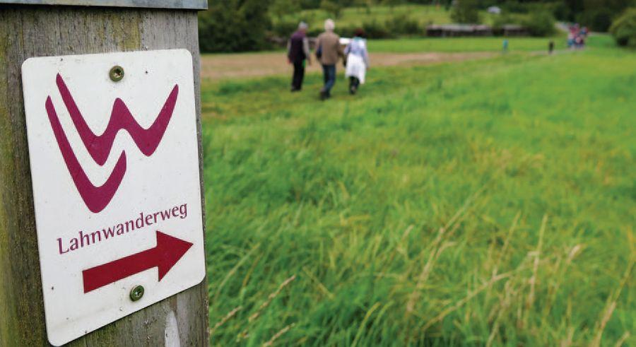 Wanderer auf einer Wiese - im Vordergrund ein Wegweiser des Lahnwanderwegs