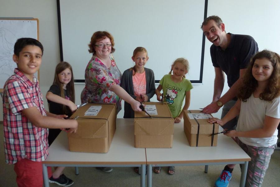 Kinder und Mitarbeiter der Stadtbibliothek öffnen Kisten mit neuen Seitenland-Heften