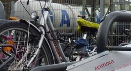 Abgestellte Fahrräder mit dem Ausschnitt eines Hinweisschildes