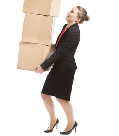 Eine Frau trägt gestapelte Umzugskartons