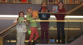 Kinder mit Büchern auf der Treppe in der Stadtbibliothek