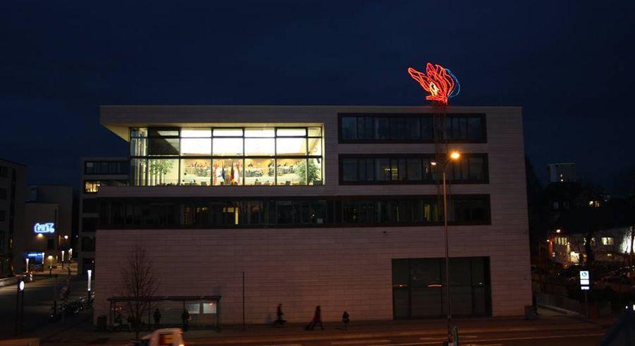 Blick auf das Rathaus mit der Installation von Knut Eckstein an der Fassade (the flame)