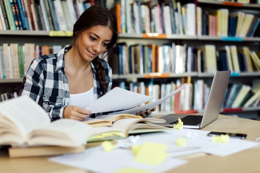 Studentin in einer Bücherei mit vielen Arbeitsunterlagen auf dem Tisch