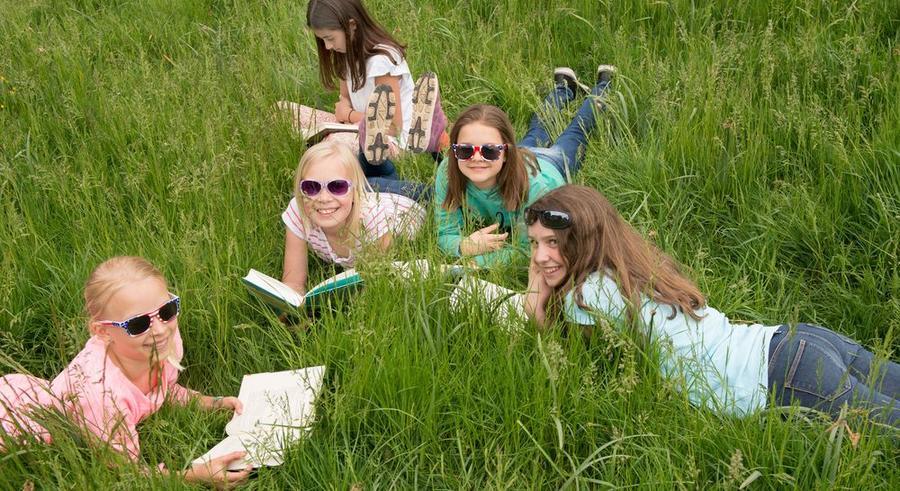 Junge Mädchen liegen in einer Wiese und lesen