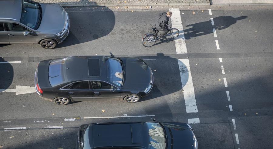 Fahrradfahren in der Stadt - Fahrradfahrer zwischen Autos an einer Ampel