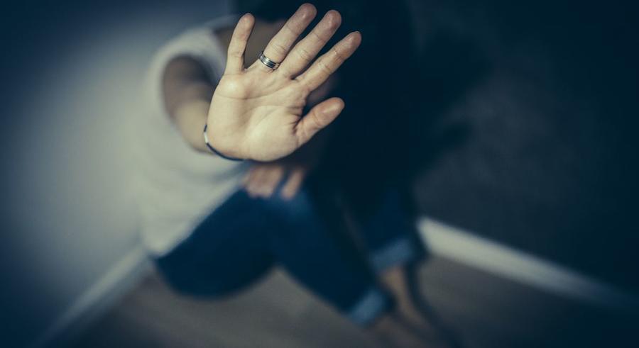 Frau kauert in einer Ecke und hält die Hand schützend hoch