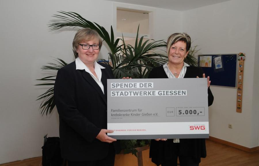 SWG-Unternehmenssprecherin Ina Weller (links) übergibt eine Spende an Beate Steinmüller vom Familienzentrum für krebskranke Kinder
