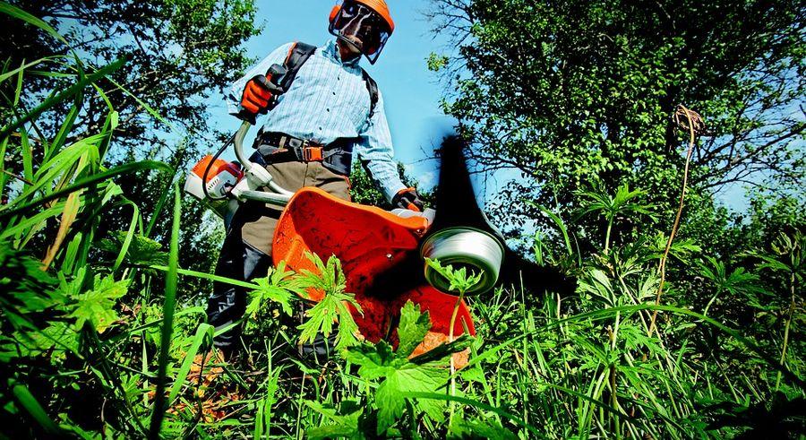Mann mit Rasenmäher bei der Gartenarbeit