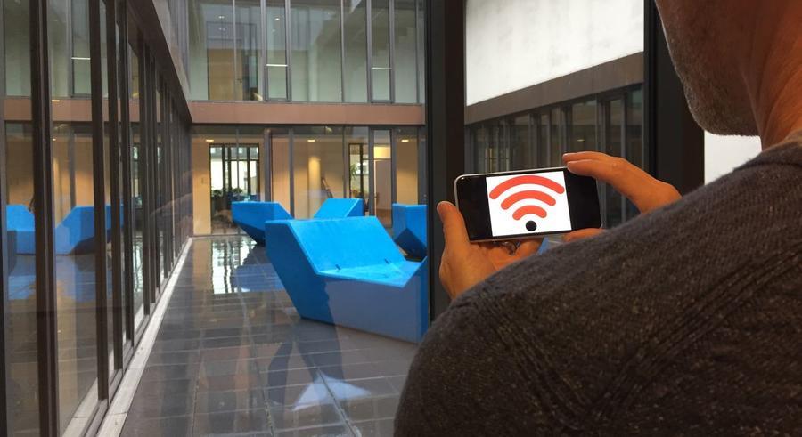 WLAN im Rathaus - Besucher schaut auf sein Smartphone