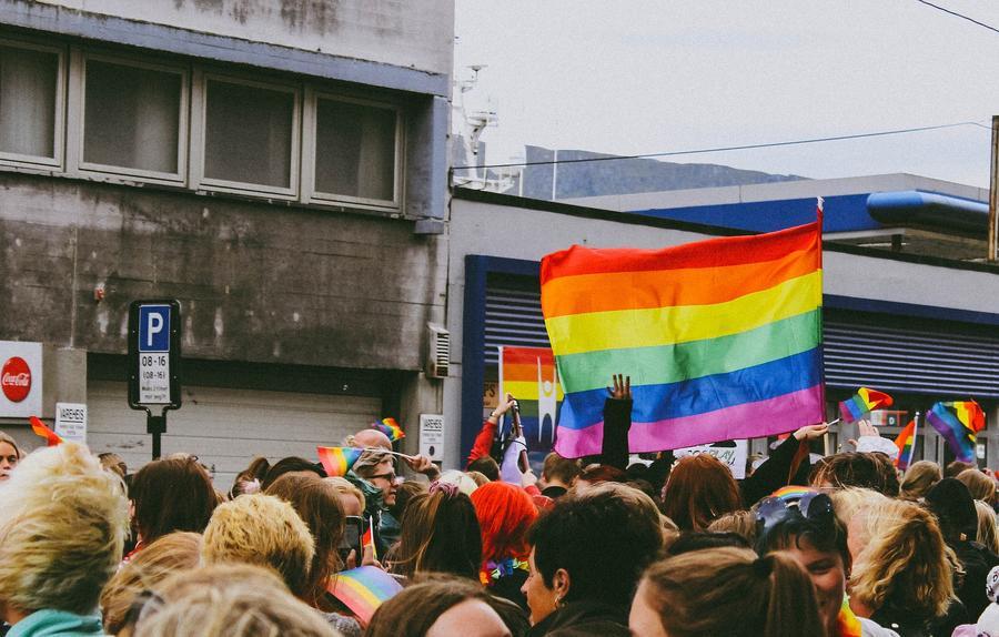 Menschen demonstrieren mit Regenbogenfahne