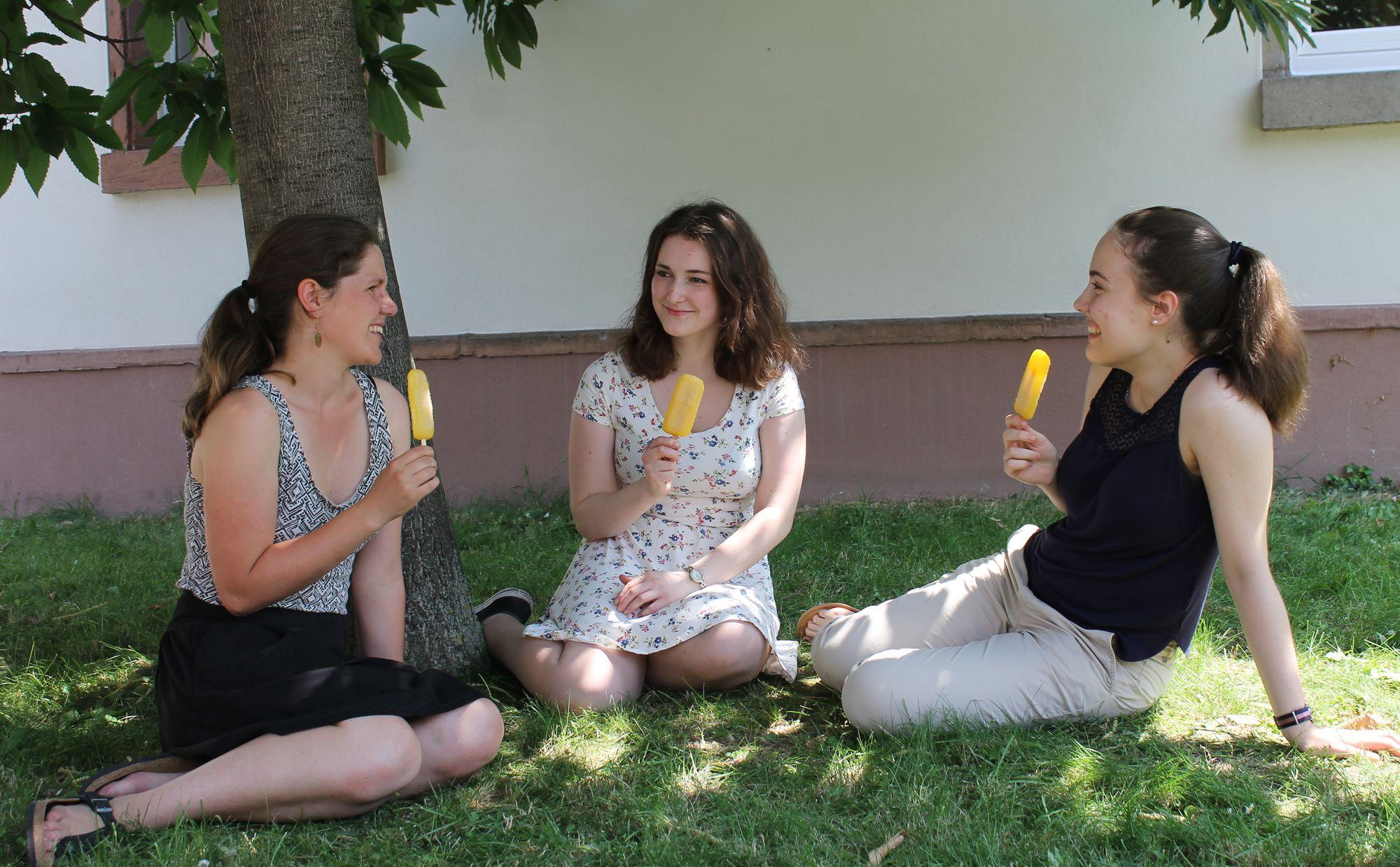 Drei junge Frauen essen ein Eis vor dem Mathematikum