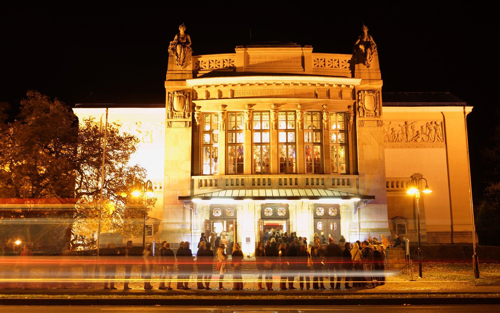 Beleuchtetes Stadttheater bei Dunkelheit